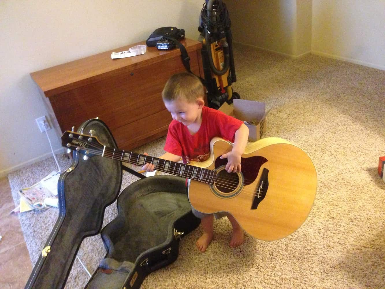 Kid holding a big guitar -Mike Levitsky
