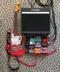 Picture of a guitar next to a fender amp and a pedal board