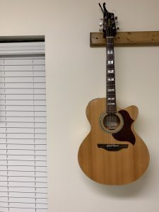 Takamine guitar hanging on a wall